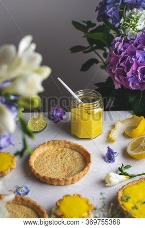 Lemon Meringue Tart On The Table With Flowers, Lemon Curd Jar