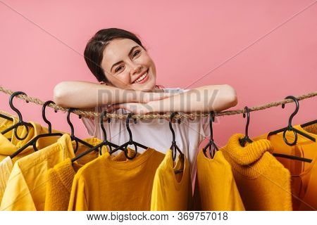Photo of nice cheerful woman smiling and looking at camera while leaning on clothes rack in studio
