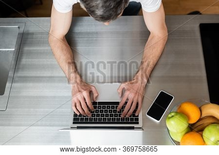 Overhead View Of Freelancer Using Laptop Near Smartphone And Fruits On Kitchen Worktop