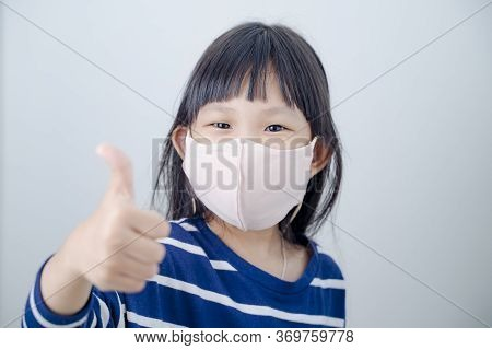 Coronavirus Covid-19.stay At Home Stay Safe Concept.little Asian Girl Wearing Mask For Protect.show
