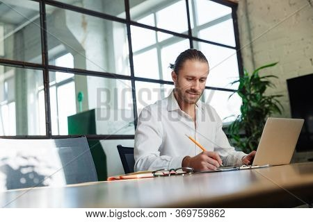 Photo of handsome pleased man with stubble making notes and working with laptop at table in modern office