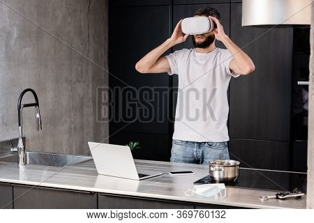 Man Using Virtual Reality Headset Near Digital Devices And Medical Mask On Kitchen Worktop
