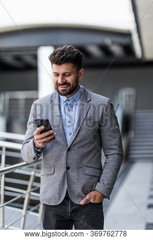 Handsome Caucasian Businessman Dressed In The Suit Reading With His Smart Phone In Office
