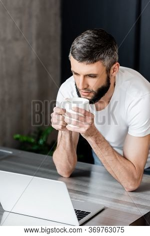 Handsome Man Holding Cup And Looking At Laptop On Kitchen Worktop