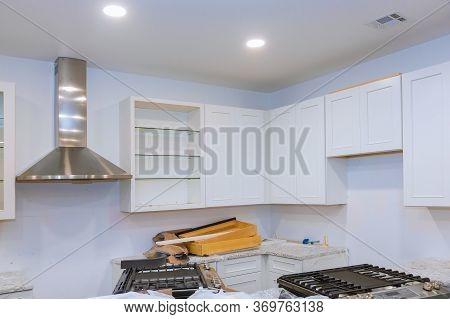Installing New Kitchen Hood In Modern Installation Of Custom Kitchen Cabinets