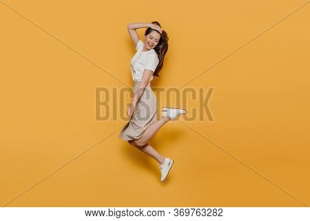 Cheerful Pretty Brunette In White T-shirt, Beige Skirt And White Sneakers, Jumping High, Careless Mo