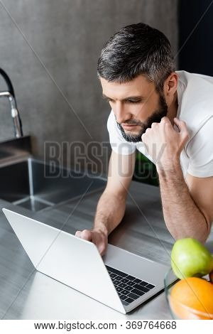 Selective Focus Of Handsome Freelancer Using Laptop Near Fruits On Kitchen Worktop