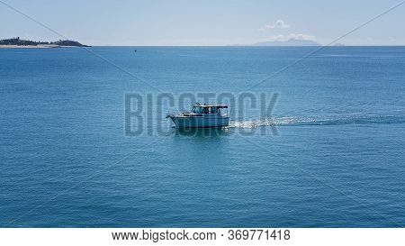 A Fishing Boat Heading Back To The Marina After A Day Out On The Water Of A Glistening Sea