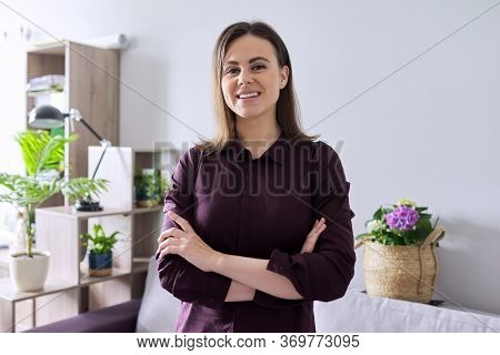 Portrait Of Smiling Beautiful Confident Woman 25 Years Old Looking At The Camera With Arms Crossed