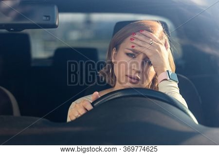 Exhausted Young Woman Driver Sitting In Her Car, Feeling Emotional Burnout After Work, Looking At Ca