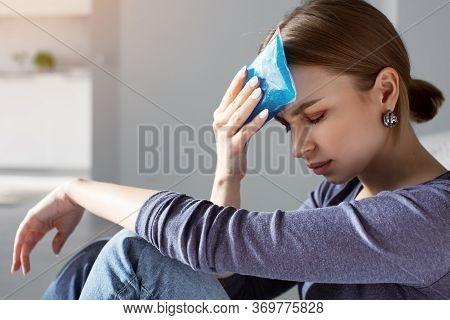 Woman Applying Ice Pack As Cold Compress On Forehead Due To Headache, Migraine, Tired After Work, Si