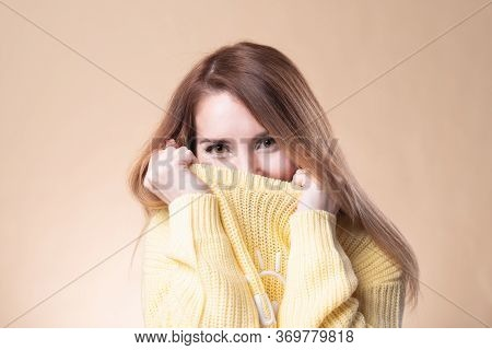 Close-up Smiling Pretty European, Brown Hair, Pull Sweater On Face And Smiling With Eyes, Playfully
