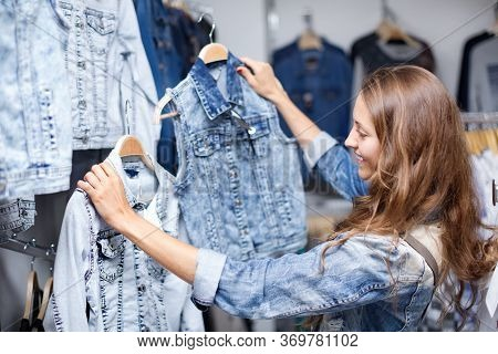 Smiling Woman Selecting Waistcoat In Commercial Centre
