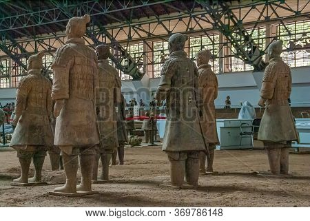 Xian, China - May 1, 2010: Terracotta Army Excavation Site. Group Of Beige-gray Statues Of Soldiers