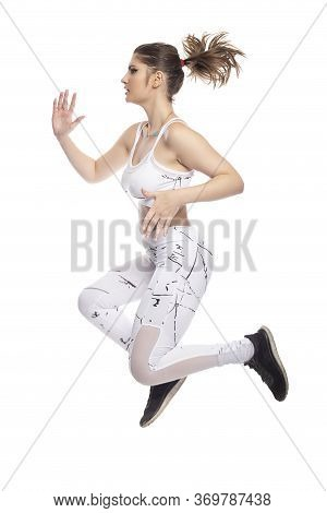Female Model Wearing Active Wear Exercising And Leaping Or Jumping Forward From A Running Pose.  She