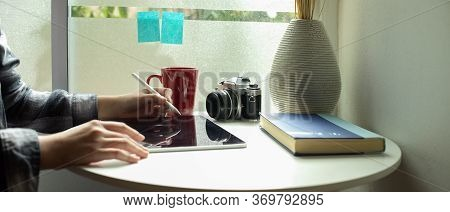 Female Freelancer Working With Digital Tablet On Coffee Table Beside Window In Living Room