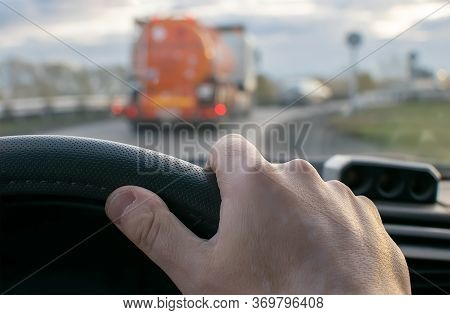 View Of The Driver Hand At The Wheel Of A Car Against The Background Of A Fuel Tanker Driving In Fro