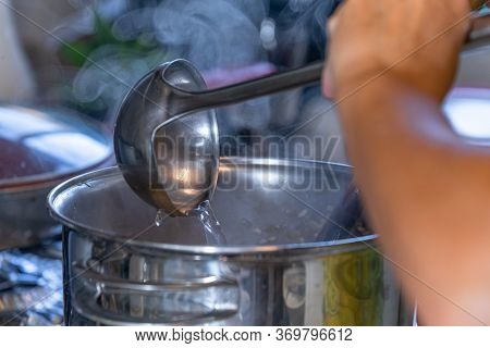 Stirring The Risotto Rice In The Pan With Hot Water.