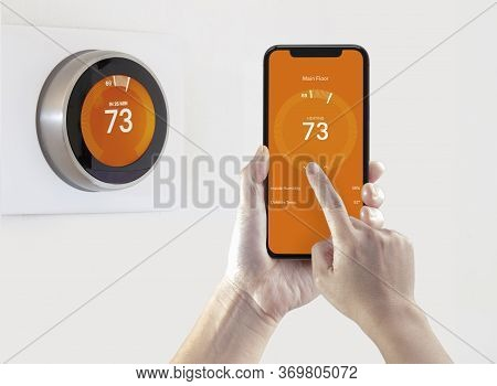 A Person Using A Smart Phone Application Warming Up The Room Temperature With A Wireless Smart Therm