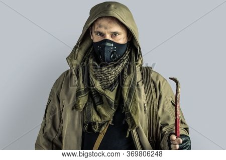 Man With Burglar Crowbar Wearing Black Protactive Face Mask And Jacket With Hood On Gray Background