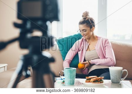 Young Woman Vlogging With A Cup Of Tea And Sandwiches On Table While Wearing Eyeglasses And Holding