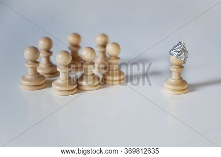 Afraid Pawn Chess Piece With A Tin Foil Hat Stands Towards A Group Of Pieces Without Hats, Conspirac