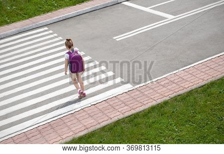 Schoolgirl Crossing Road On Way To School. Zebra Traffic Walk Way In The City. Concept Pedestrians P