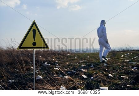Yellow Triangle Warning Sign About Danger And Hazards In Field With Trash. Back View Of Environmenta