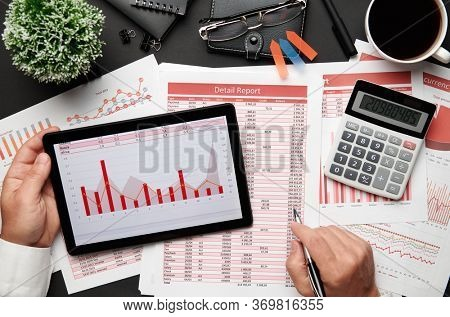 Top view of businessman's hands working with tablet pc and financial reports. Modern black office desk with notebook, pencil and a lot of things. Flat lay table layout.