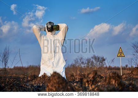 Male Environmentalist Clutching His Head In Despair While Sitting At Damaged Grass And Soil After Fi