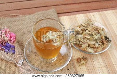 Glass Of Chrysanthemum Juice With Dried Chrysanthemum Flower On Sack And Wood Mat Background.