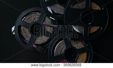 Coils Of Rgb Led Strip On A Black Table. Led Strip For Creative Lighting Collected In A Black Coil,