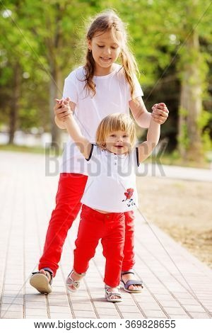 Toddler Girl And Her Older Sister Walking In The Park