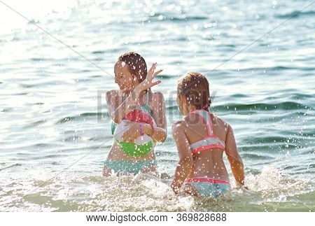 Two Girls Are Playing In Sea With Splashes