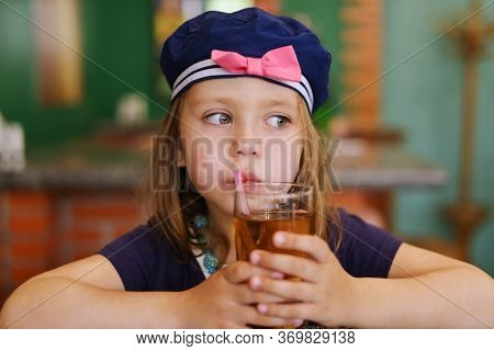 Happy Child Girl Drinking Juice In A Cafe