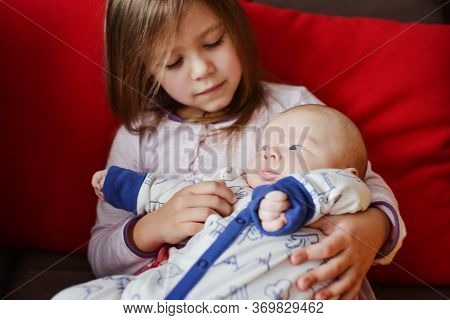 Little Sister  Holding And Hugging Her Newborn Brother In Soft Focus