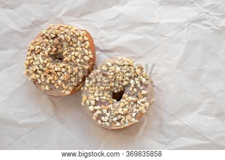 Brown Glazed Donuts Sprinkled With Nuts On Crumpled Beige Paper Background. Unhealthy High-calorie F