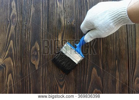 A Worker Painting A Wooden Wall. A Man Holding Brush. A Hand Of Worker Painting Wooden Plank. A Pain