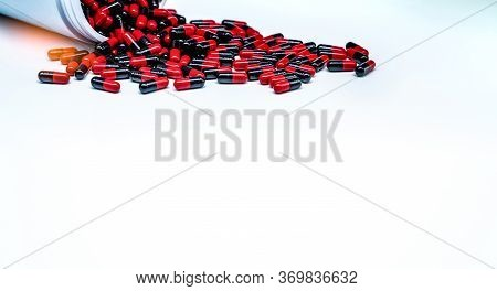 Red-black Antibiotic Capsule Pills Spread Out Of Plastic Drug Bottle On White Background. Antibiotic