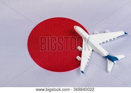 Japan Flag And Toy Airplane Close Up. Concept Of Air Travel To Japan. Travel To Japan After Quaranti