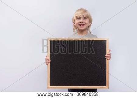 Fair-haired Boy Holding Blackboard And Smiling On White Background. Copy Space. Template. Mockup