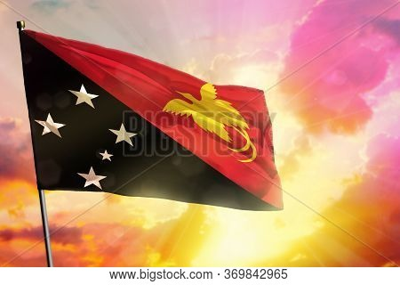 Fluttering Papua New Guinea Flag On Beautiful Colorful Sunset Or Sunrise Background. Papua New Guine