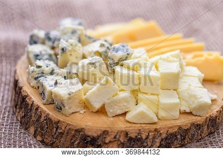 Natural Cheeses Slices, Side View. Pieces Cheese On Natural Background. Cheese With Mold Close-up. D