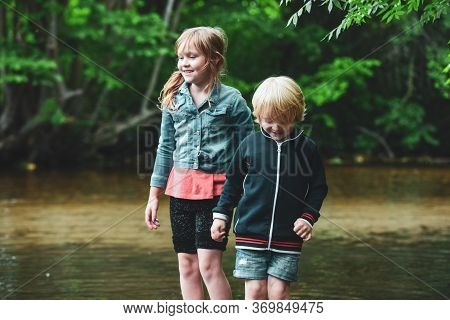 Children Paddle In A Stream Of Water Outside During A Sunny Day Out Together