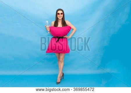 Happy Woman In Pink Pillow Dress And Sunglasses Holding A Glass Of Champagne On A Blue Background Fo