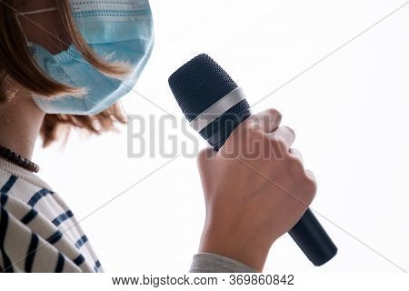 Close Up Of Musician Wearing Medical Face Mask And Holding Microphone Isolated On White Background.