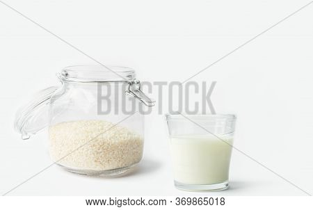Glass Of Non-diary Animal-free Plant Based Milk Dry Rice In Crystal Jar On Shite Kitchen Table. Heal