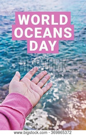 Open Palm And Text World Oceans Day On Surface Of Ocean Water. Ocean Protection Concept. World Ocean