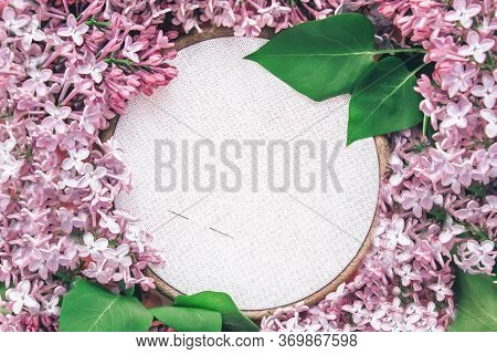White Canvas For Cross Stitching In A Wooden Hoop Among Beautiful Spring Flowers Of Lilac, Needle, P