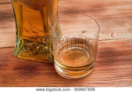 A Glass And A Decanter With Whiskey Stand On A Wooden Table. A Glass Of Whiskey Without Ice.
